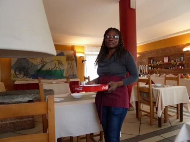 Emanuela, rifugiata politica, originaria della Costa d'Avorio, serve ai tavoli.
