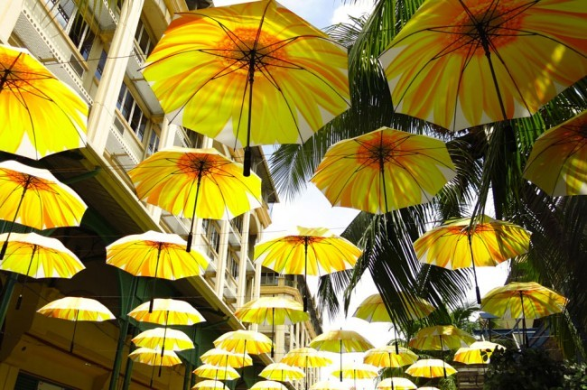Ombrelli come copertura. Riparano dal sole e dalla pioggia nella zona pedonale dedicata allo shopping a Le Caudan Waterfront. Foto Roberto Savioli