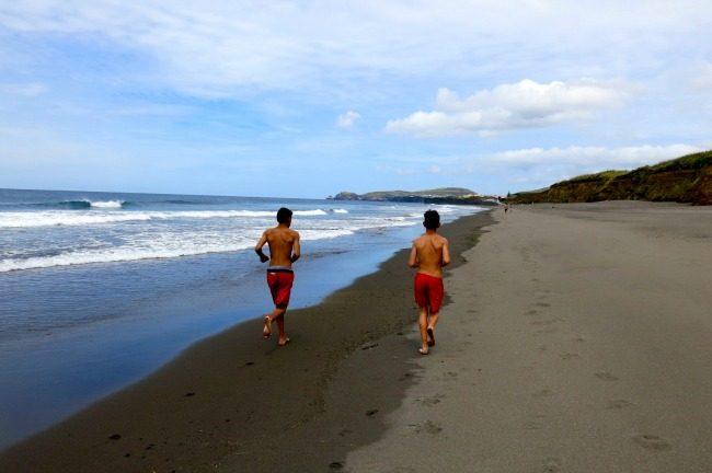 Due ragazzini di corsa sulla spiaggia vulcanica di Santa Barbara.