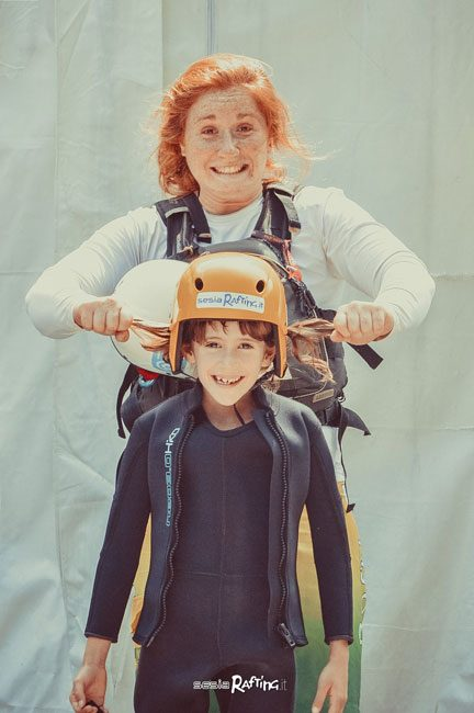 Jusmine, una delle guide di hydrospeed sistema il casco ad un ragazzino.