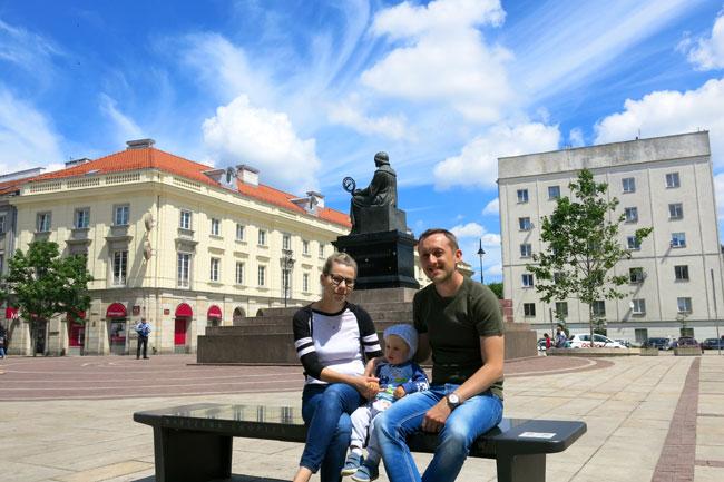 """Una famiglia seduta su una delle """"Panchine di Chopin"""". Alle spalle il monumento a Copernico."""